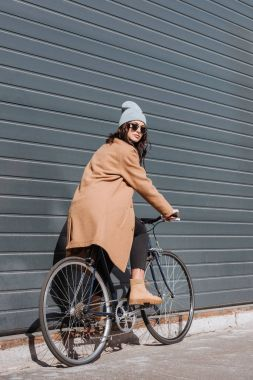 Woman in autumn outfit sitting on bicycle
