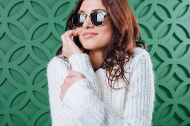 Woman in sweater and sunglasses talking by smartphone