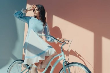 Woman in fashionable turquoise dress with bicycle