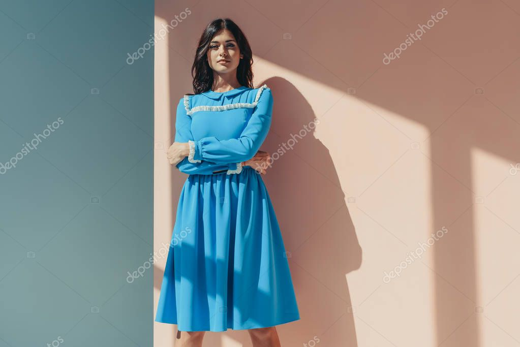Beautiful woman standing in fashionable turquoise dress with long sleeves and looking at camera stock vector