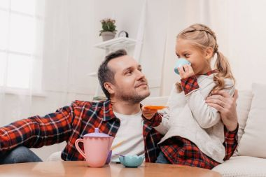 child having tea party with father