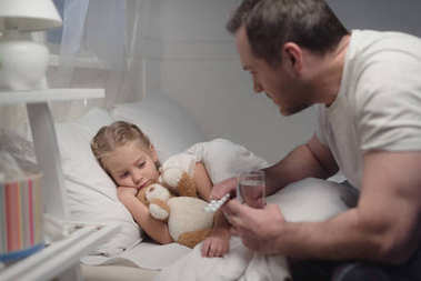 father giving pills to sick daughter