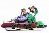 Paar in Snowboardkostümen mit Snowboards