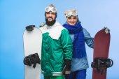 glückliches Paar mit Snowboards