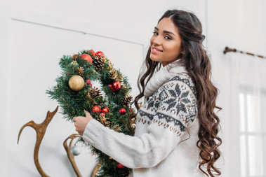 woman holding christmas wreath
