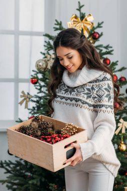 woman with box of natural christmas decor
