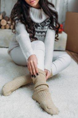 woman putting on warm socks
