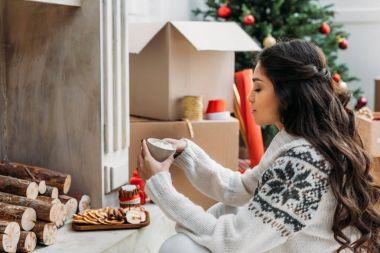 woman with mug of hot drink on christmas