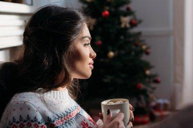 woman enjoying hot chocolate on christmas