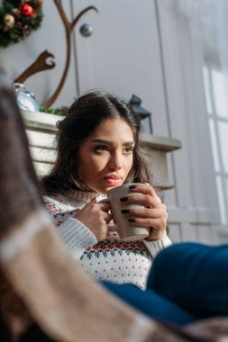 Thoughtful young woman with cup of hot drink in warm sweater stock vector