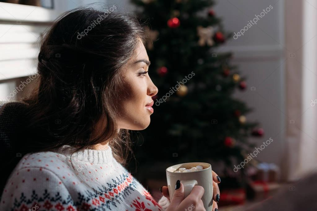 woman enjoying hot chocolate on christmas