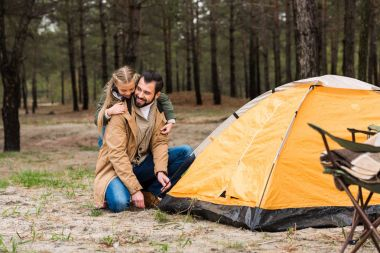 Happy father and daughter installing tent for camping stock vector