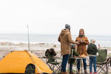family having camp on seashore