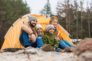 family sitting near tent
