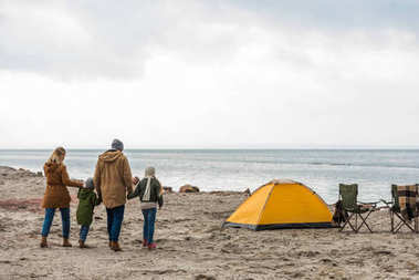family walking to tent on seashore