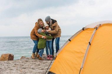 happy family camping on seashore