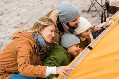 family looking at camping tent