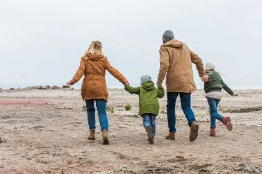 family holding hands and walking by seashore