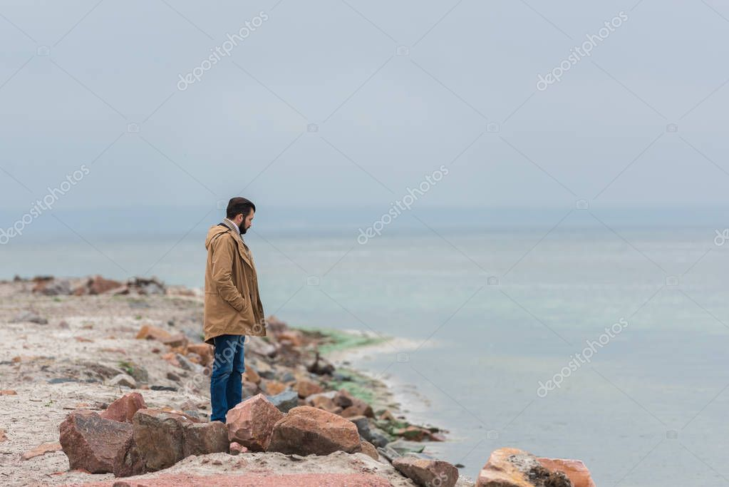 man standing on seashore
