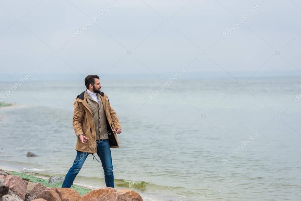 man throwing stones into sea
