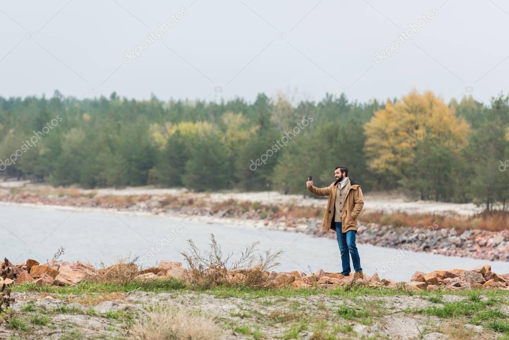 man taking photo of landscape with smartphone