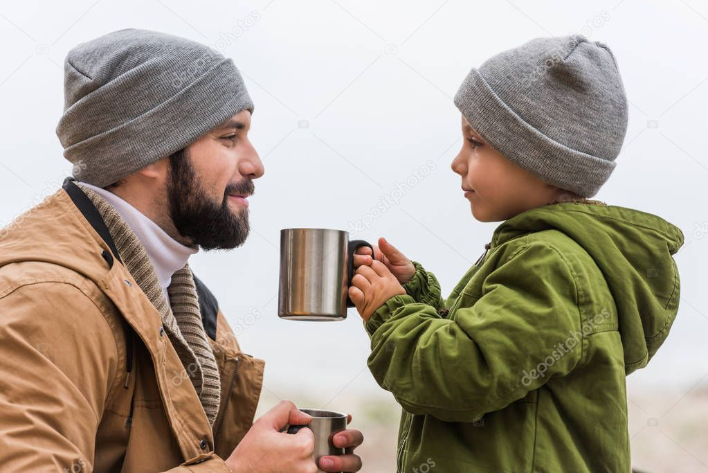 father and son with hot drinks outdoors