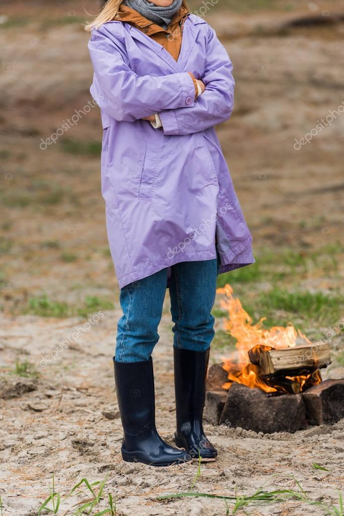 lonely woman in raincoat near bonfire