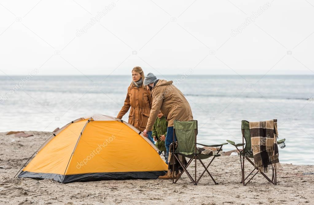 family looking at camping tent on seashore