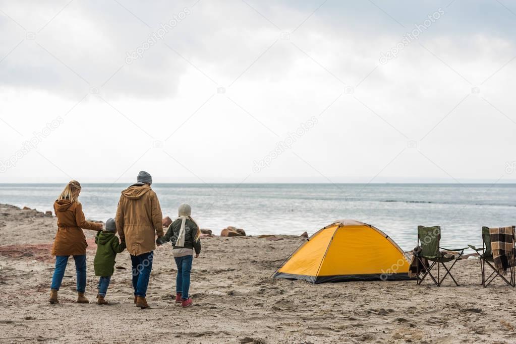 family walking to tent on seashore