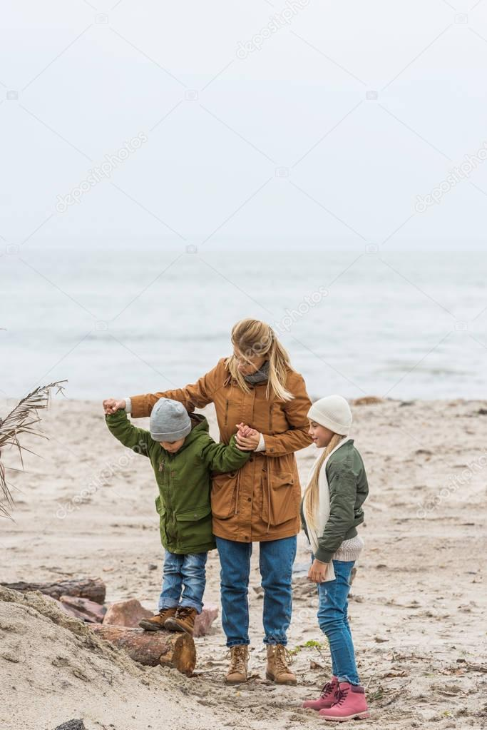 mother and kids on seashore