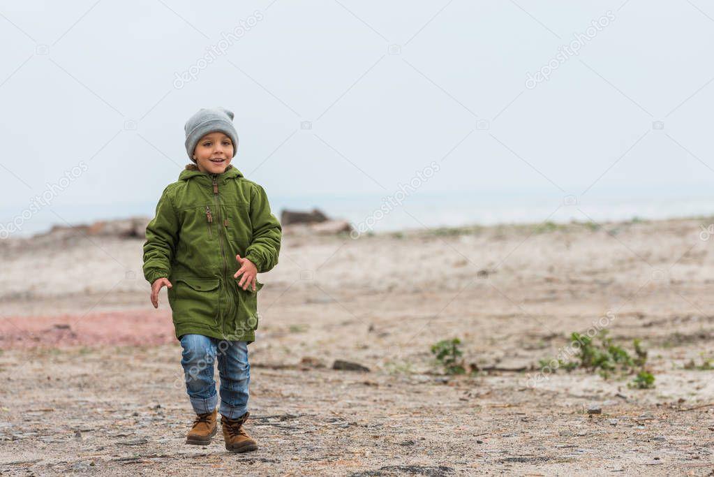 boy running by seashore