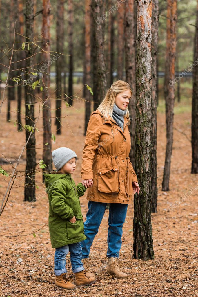 mother walking by forest with son