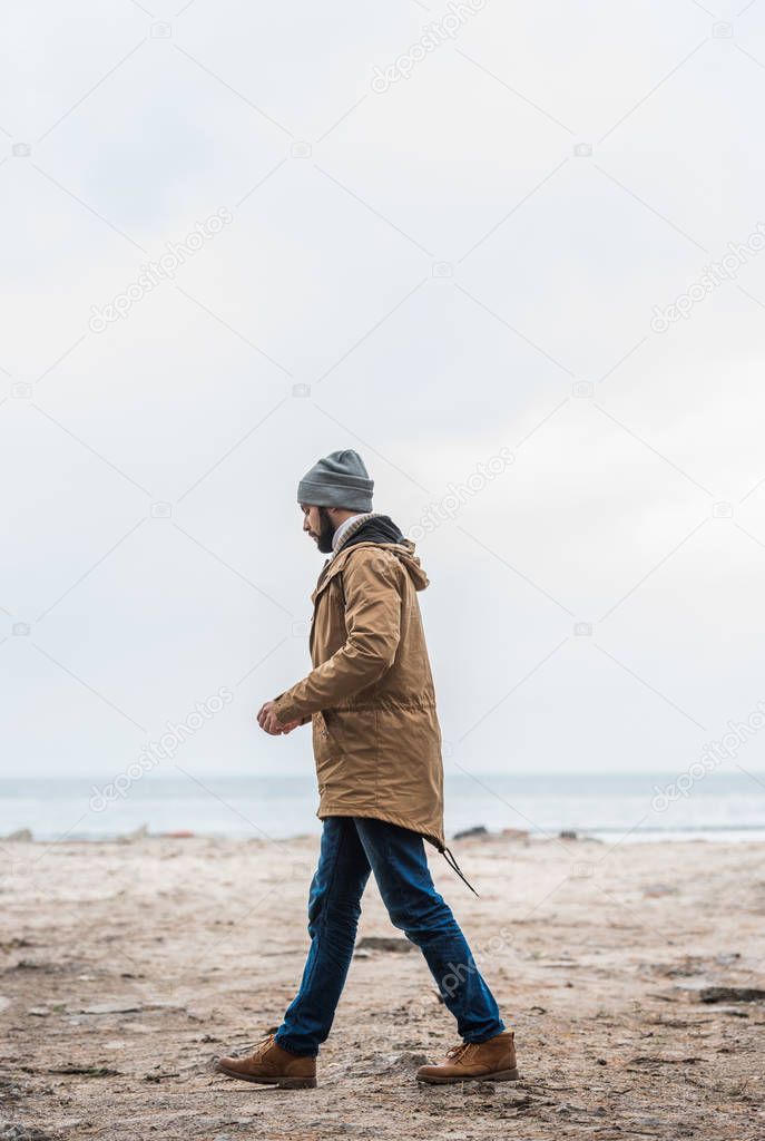lonely man walking by seashore