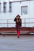 Žena v podzimní oblečení, stojící na střeše