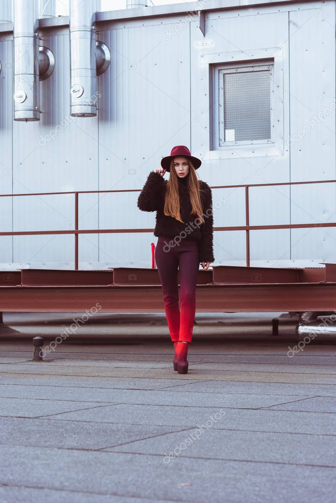 woman in autumn outfit standing on roof