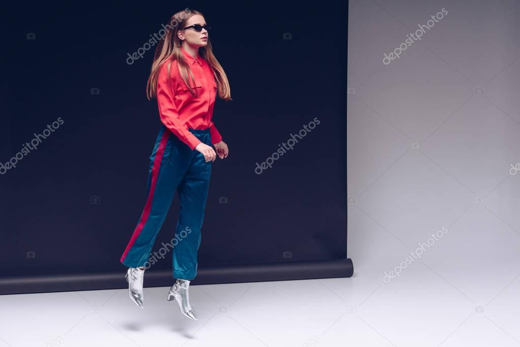 Beautiful girl jumping in red shirt and black sunglasses stock vector