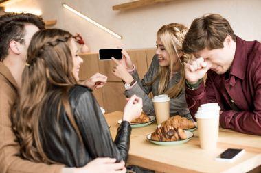 Girl showing something on smartphone