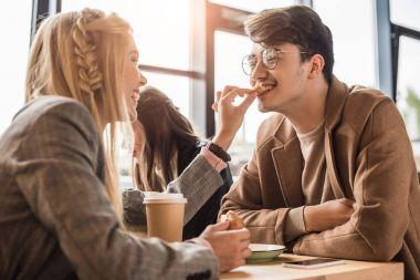 Girlfriend giving piece of croissant to boyfriend