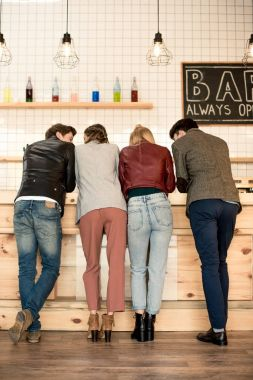 people standing at wooden bar counter
