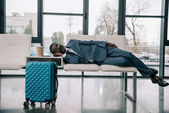 Photo businessman napping on chairs at airport