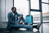 Fotografia uomo daffari che si siede sul pavimento allaeroporto