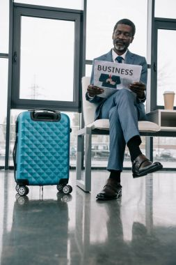 Businessman reading newspaper in airport