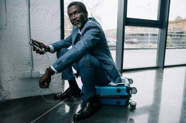 businessman waiting smartphone charging at airport