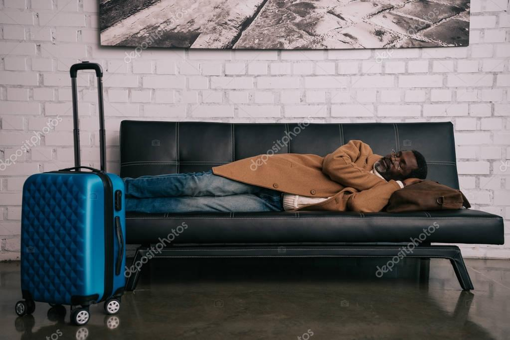 man napping on black sofa