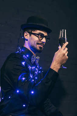 man with champagne and christmas lights