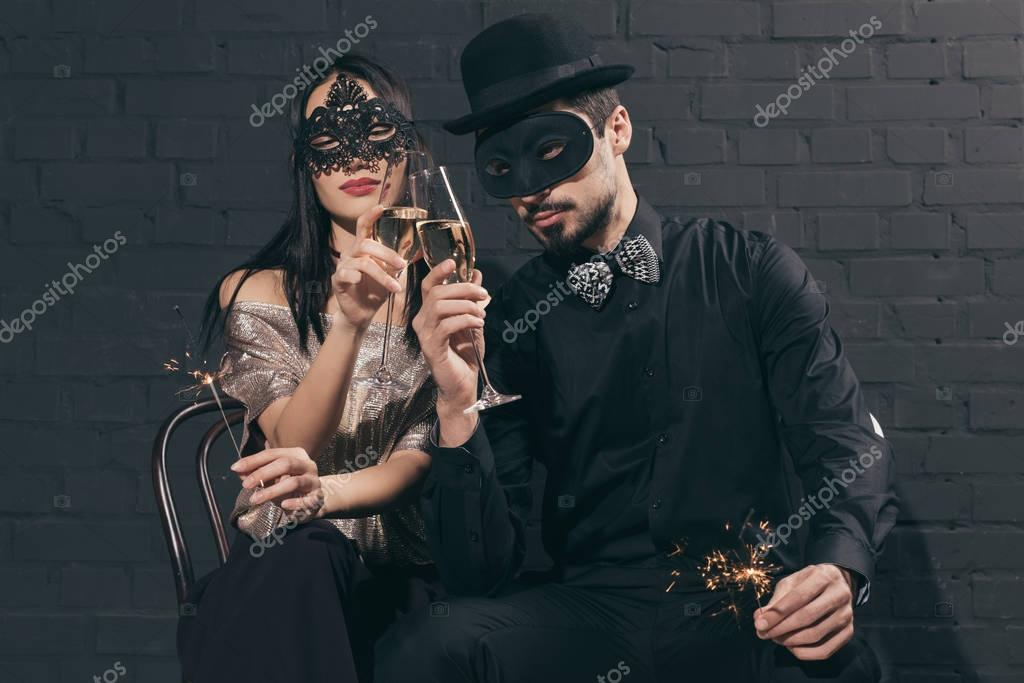 multicultural couple in christmas masks with sparkles
