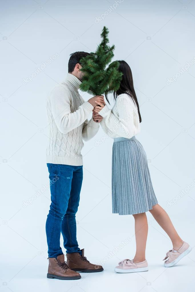 couple holding christmas tree