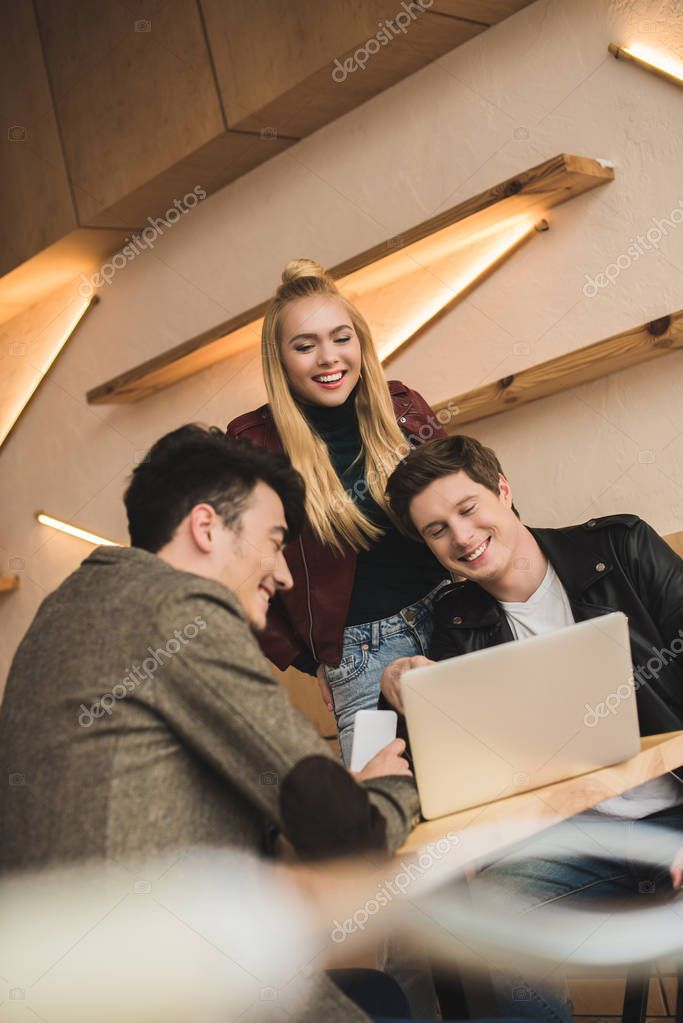 Friends laughing and looking at laptop