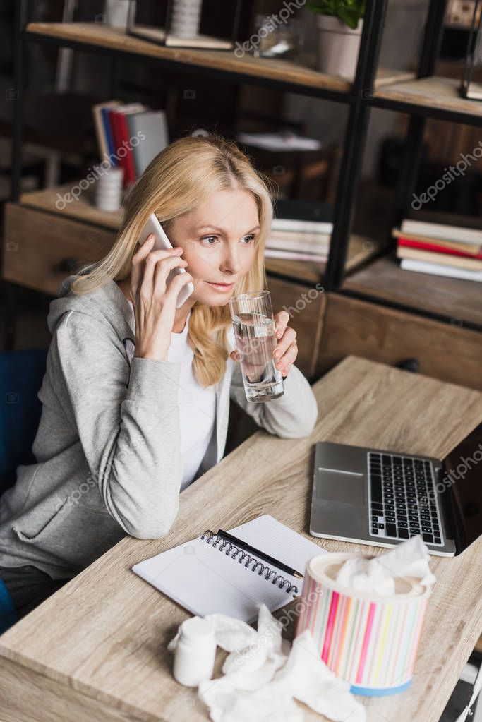 woman drinking water and talking on smartphone