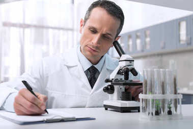 Professional lab technician taking notes while doing microscope sample analysis stock vector